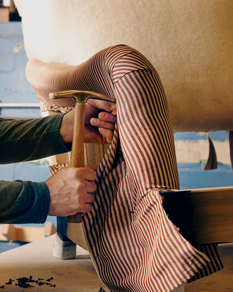 Construction on a chair in the George Smith furniture workshop, using a specality tool to create pleats and folds