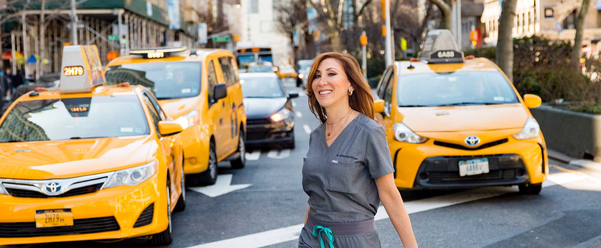 Dr. Alisa Kauffman, geriatric house call dentist crossing the street in New York City.