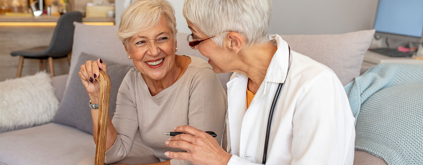 Female resident with cane having a conversation with female care provider in a comfortable setting