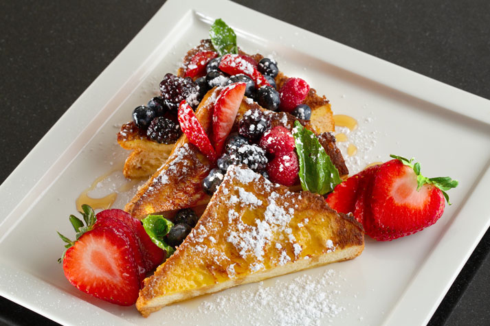 French toast topped with strawberries, raspberries, blackberries and powdered sugar