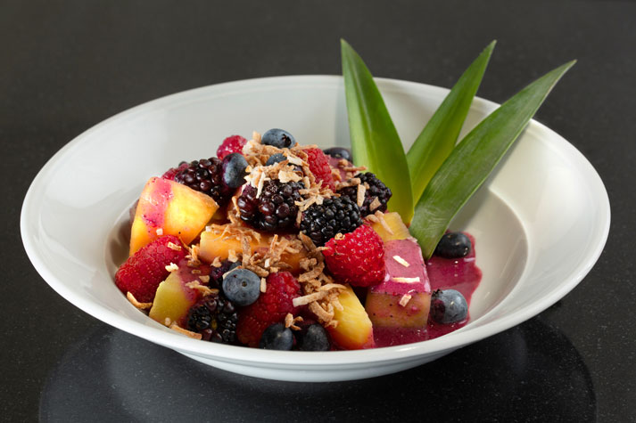 Seasonal fresh fruit salad with mango, pineapple, and berries, garnished with coconut and aloe leaves