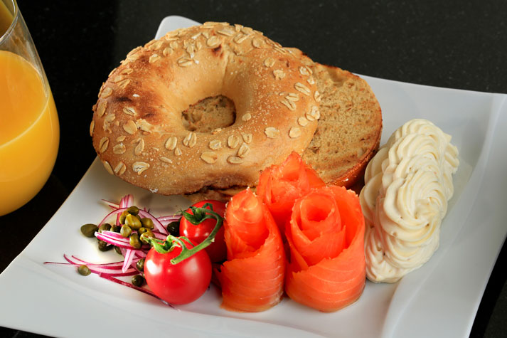 Bagel with ornately designed lox and cream cheese, served with cherry tomatoes, red onions, and capers, with glass of OJ