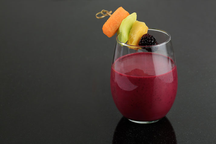 Red fruit smoothie in round glass topped with fresh fruit skewer