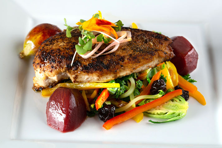 Boneless pan seared chicken breast surrounded by cucumber, shallots, and oranges, garnished with microgreens