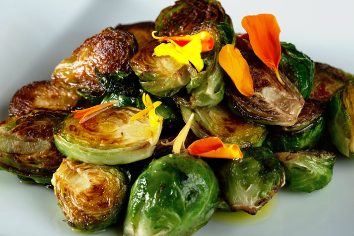Grilled Brussel sprouts garnished with orange and yellow edible flowers