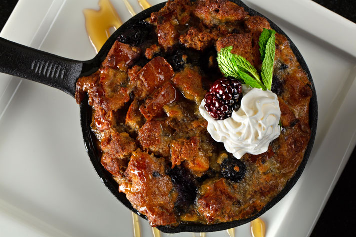 Blueberry bread and rice pudding garnished with whipped cream, blackberry and fresh leaf sprig