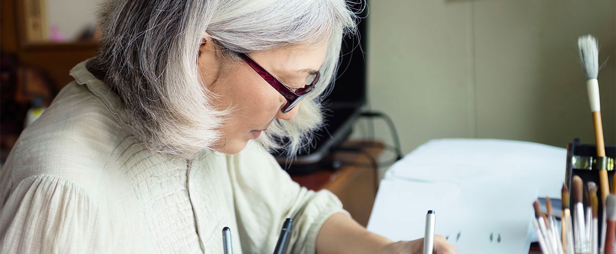 Female resident wearing glasses sitting at a desk focused on drawing