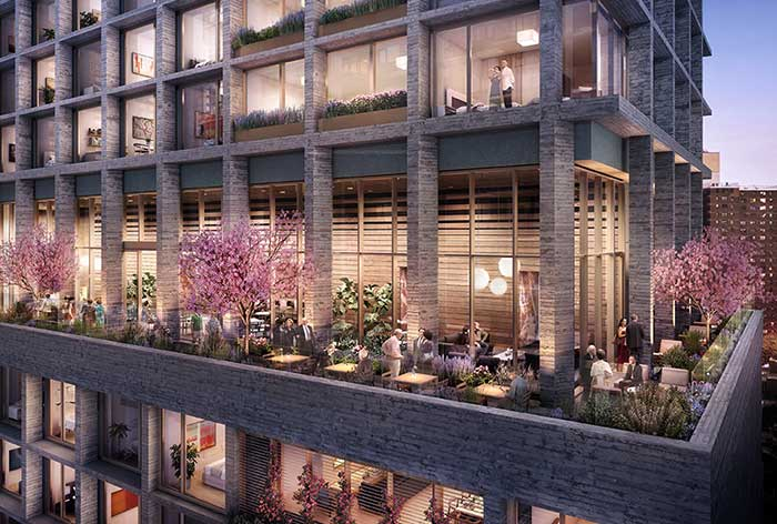 Inspire's outdoor Sky Park at dusk, featuring a wrap around area of lush greenery with family and friends enjoying the space