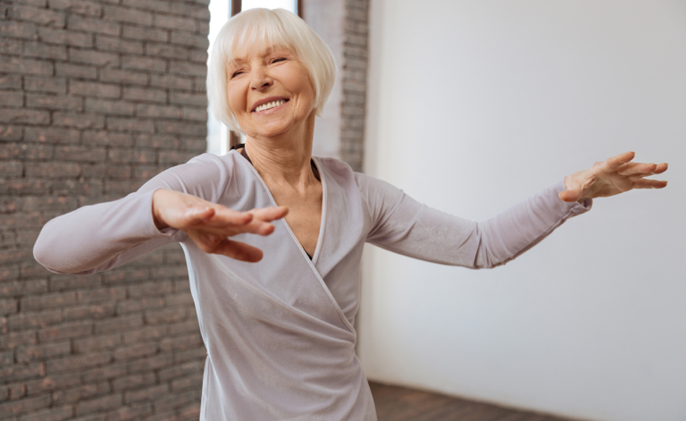 Senior aged female wearing athletic top with hands outstretched dancing