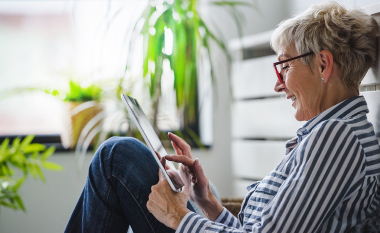 Older female women relaxing and using touch tablet