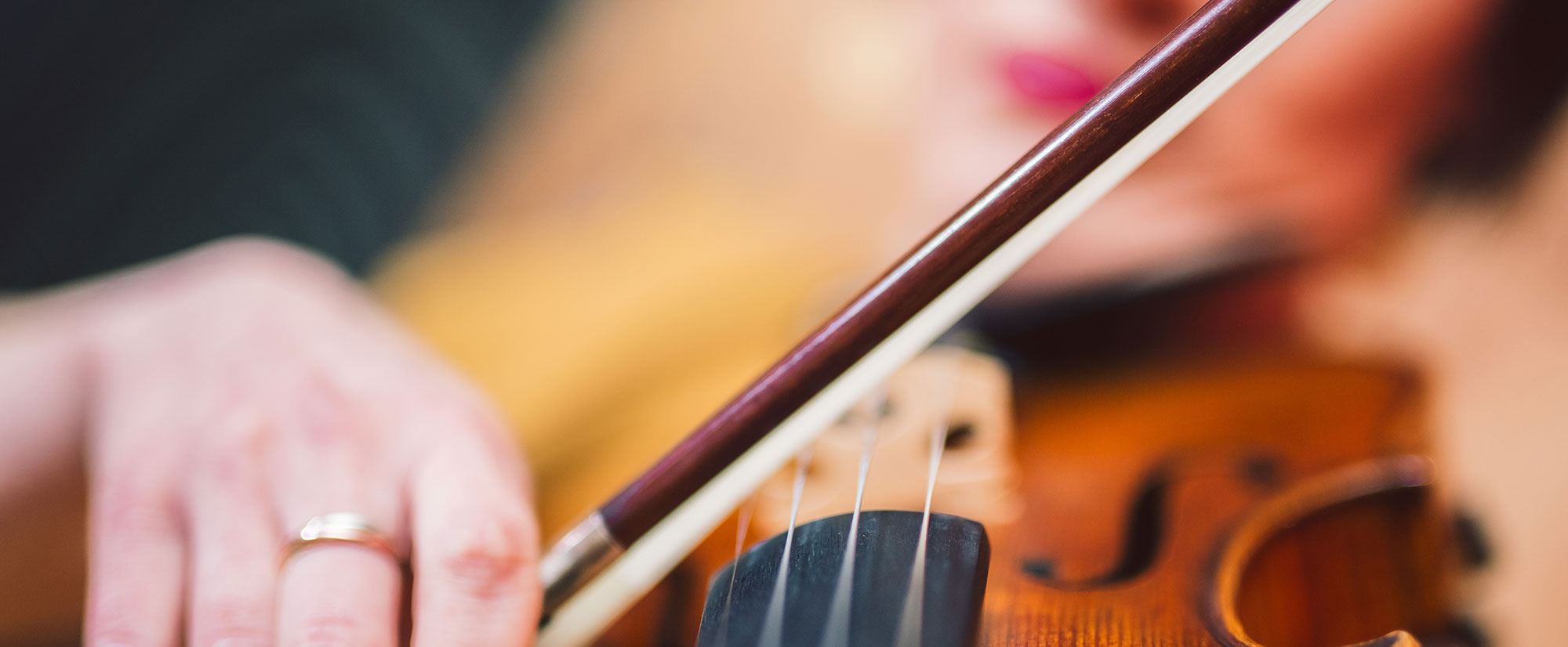 Close up of female hands playing violin with bow
