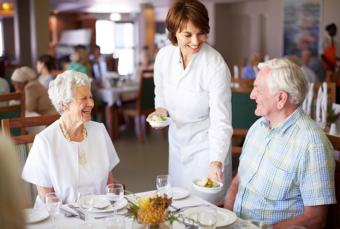 Resident couple being served by female waitstaff enjoying one of Inspires many dining options