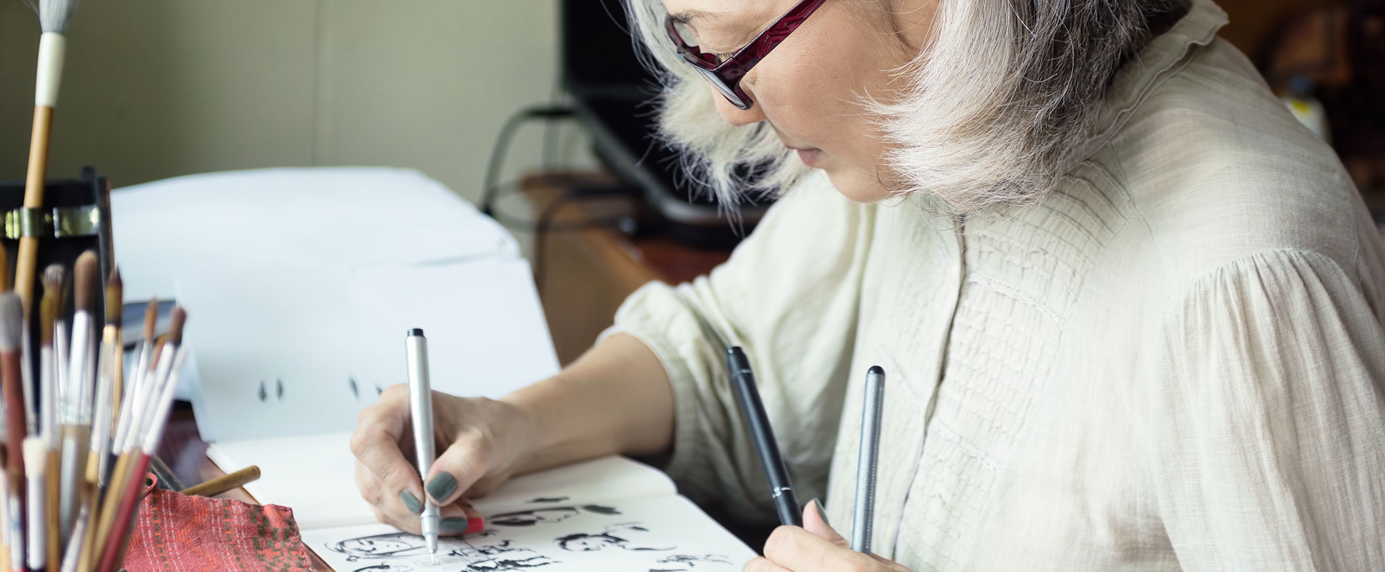 Female resident using fine tipped pen to create artwork at desk