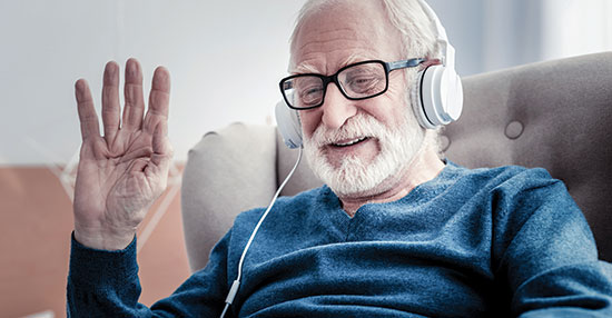 Male resident wearing headphones, enjoying the benefits of the Allī Technology Suite