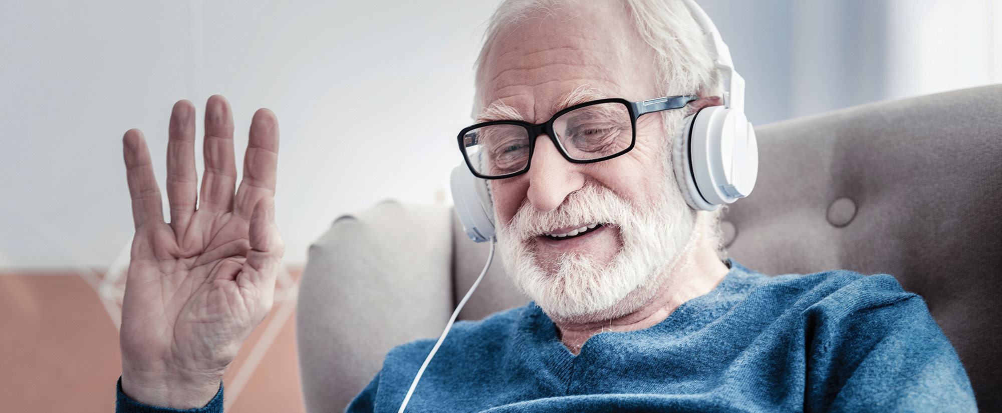 Male resident wearing headphones with hand raised, enjoying the benefits of the Allī Technology Suite