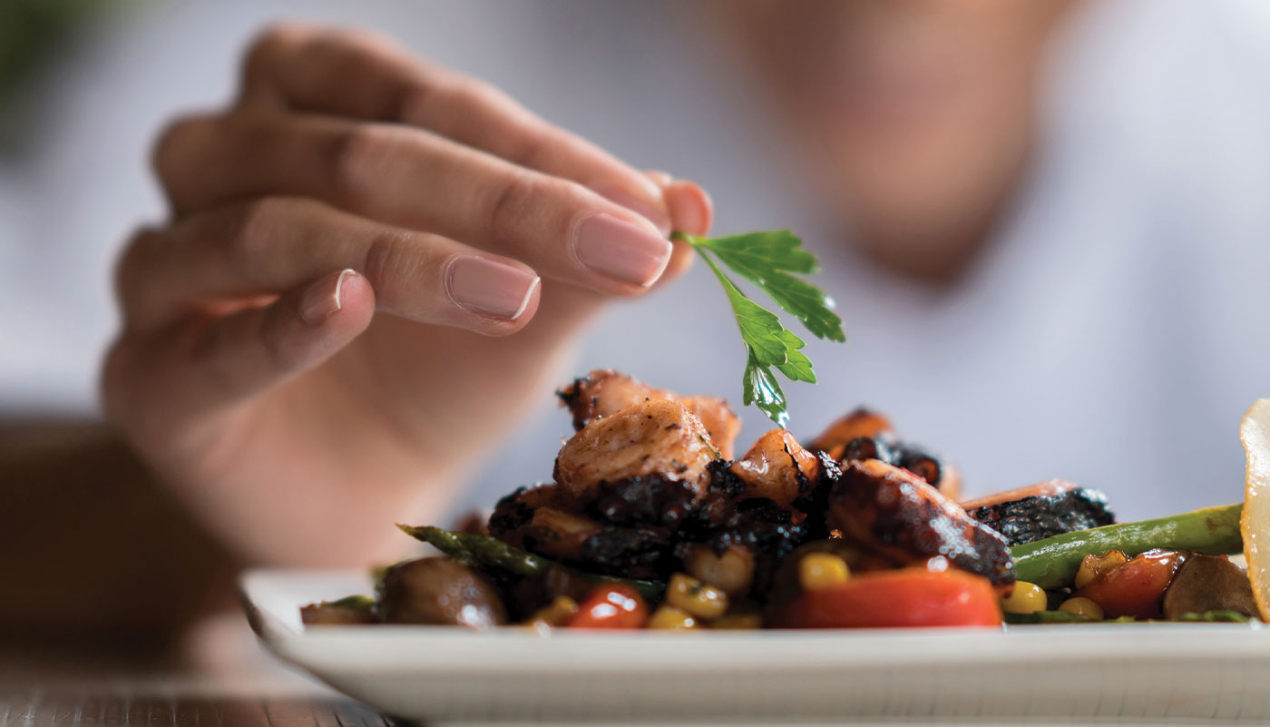 Woman's hand applying garnish to gourmet meal as part of bespoke dining program