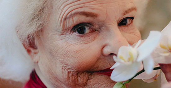 Portrait of Shirley Freitag with flower, a future Inspire resident