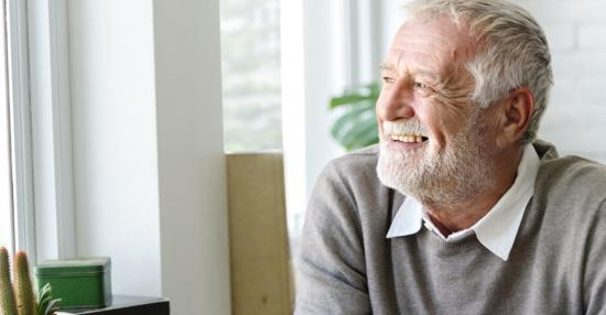 Senior male smiling in a comfortable indoor space looking outside his window