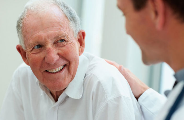 Male resident smiling while being patted on the back by male caregiver